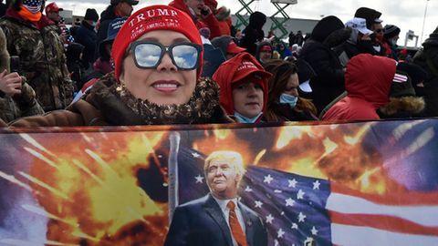 Eine Frau hält bei einer Wahlkampfveranstaltung eine Fahne auf der Ex-US-Präsident Trump zu sehen ist