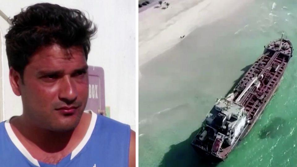 Links steht ein Mann mit schwarzen Locken und blauem T-Shirt vor einem weißen Deckshaus, rechts liegt ein Schiff am Strand