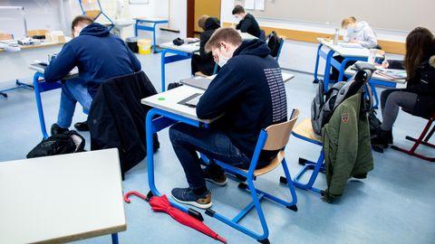 Schülerinnen und Schüler eines geteilten Kurses der Oberstufe sitzen in einem Klassenraum