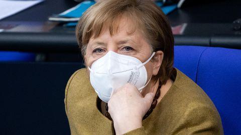 Angela Merkel sitzt mit FFP2-Maske im Bundestag und guckt in die Kamera.