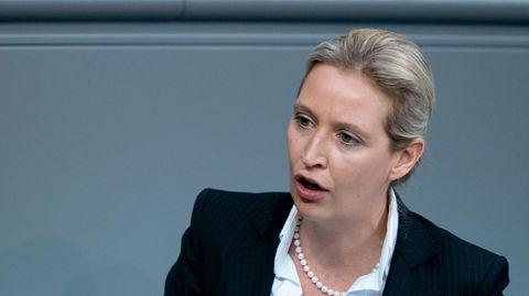 Alice Weidel steht am Rednerpult des Bundestages und gestikuliert mit der rechten Hand. Sie trägt einen dunkelblauen Blazer
