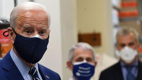 Mit schwarzem Mund-Nasen-Schutz steht US-Präsident Biden in einem Labor und spricht offenbar mit Mitarbeitern