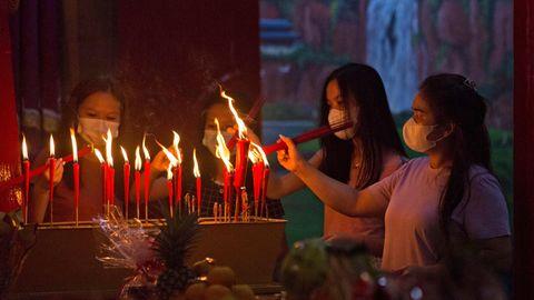Vier Jugendliche entzünden Kerzen in einem chinesischen Tempel.
