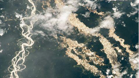 Blick aus dem Weltraum auf schimmernde Goldadern im Amazonas-Regenwald von Peru