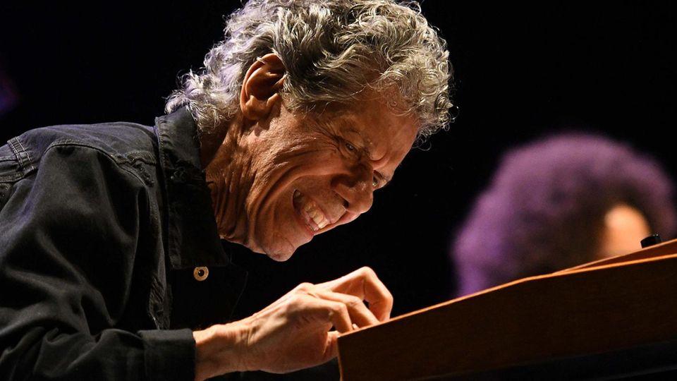 Ein älterer Mann mit grauen Locken sitzt mit konzentriertem Lächeln tief gebeugt über die Tastatur an einem Klavier