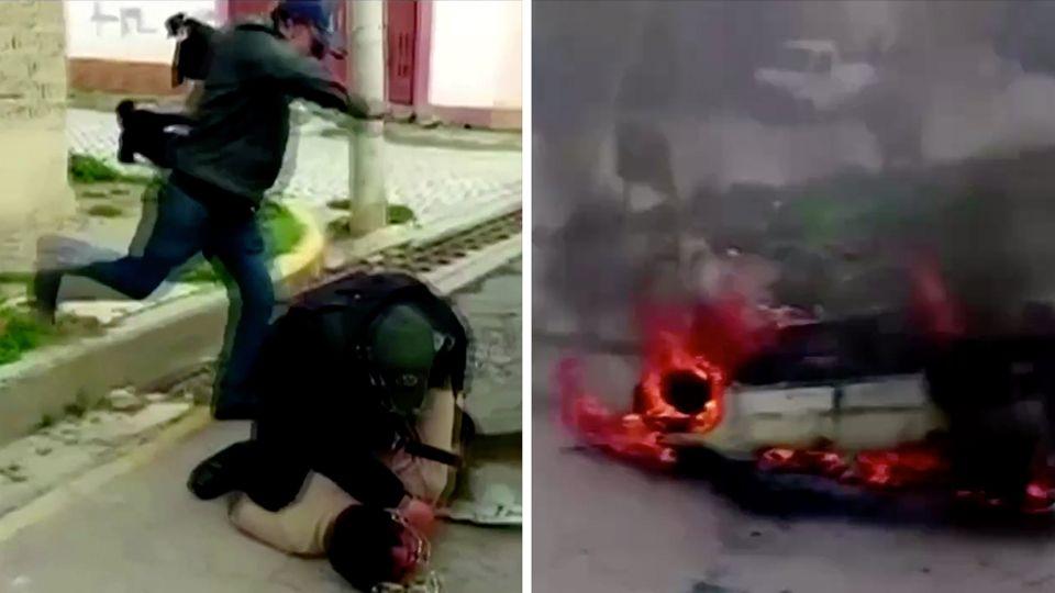 In der linken Bildhälfte tritt ein Mann auf einen am Boden Liegenden ein, rechts brennt ein auf dem Dach liegendes Auto