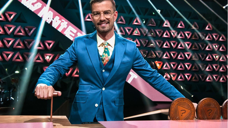 Joko Winterscheidt steht in einem blauben Anzug an einem Showpult
