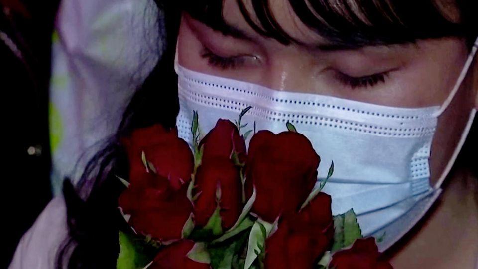 Eine Asiatin hält einen Strauß rote Rosen an ihr mit OP-Maske geschütztes Gesicht. Sie hat die Augen geschlossen