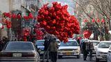 Ein Mann aus Afghanistan verkauft herzförmige Luftballons am Valentinstag