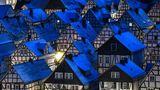 Fachwerkhäuser stehen in einer Reihe, die Dächer sind blau angeleuchtet