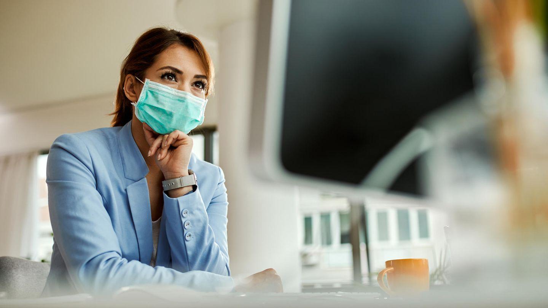 Coronavirus Ansteckungsrisiko: Eine Frau mit Maske steht in einem Büro
