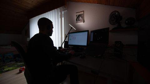 Mann arbeitet in der Dunkelheit vor einem Computer