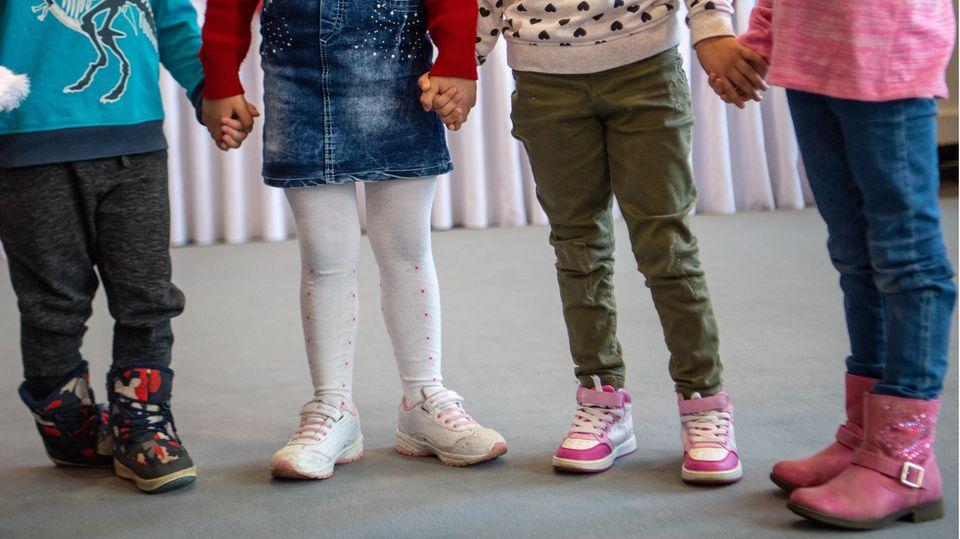 Kinder im Kindergartenalter halten sich an den Händen