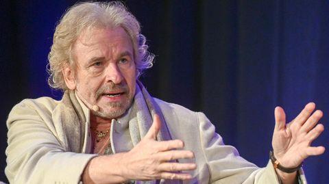 Fernsehmoderator Thomas Gottschalk sitzt auf einem Sessel und diskutiert bei einer Veranstaltung