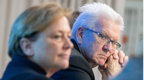 Winfried Kretschmann schaut ernst zur Seite in die Kamera, davor, unscharf: CDU-Herausforderin Susanne Eisenmann