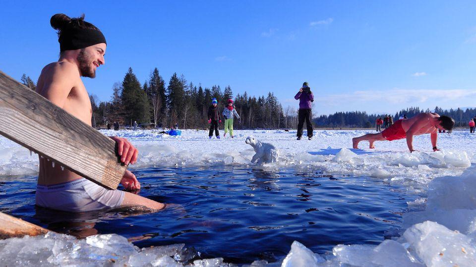 Ein junger Mann steigt im Winter zum Eisbaden in einen halb gefrorenen See.