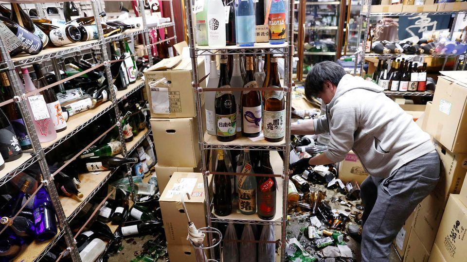 Der Inhaber eines Spirituosengeschäfts räumt nach einem starken Erdbeben in seinem Geschäft auf. Am Boden zerstörte Flasche