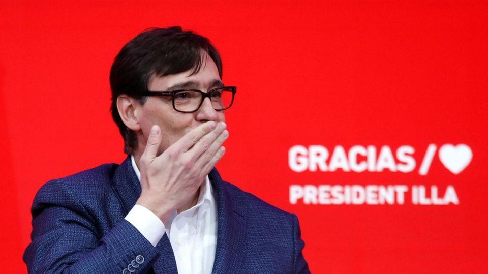 Ein Mann in blauem Anzug steht auf einem ganz in roten Podium und wirft Luftküsse ins Publikum. Er trägt eine Hornbrille