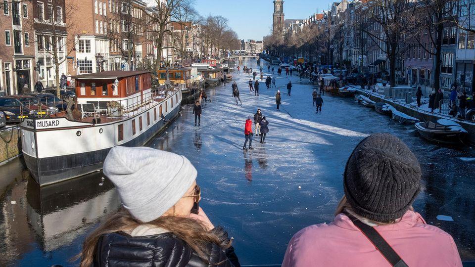 Drei Frauen in Winterkleidung schauen über ein Brückengeländer auf Eisläufer auf der Gracht unter ihnen