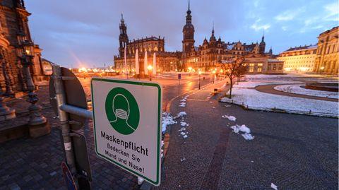 Ein Hinweisschild auf die Maskenpflicht hängt auf dem Theaterplatz in Dresden
