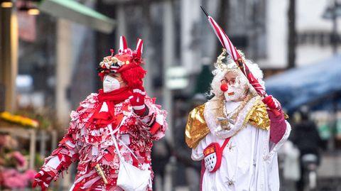 Zwei Frauen in rot und weiß gemusterten Kostümen sowie einer weißen und roten Perücke lauf