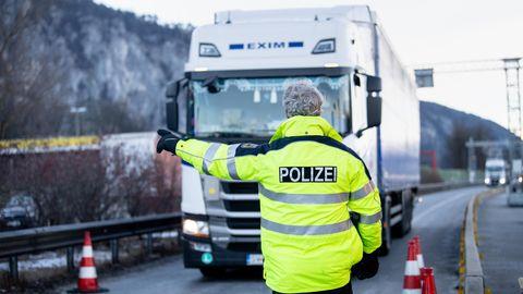 Ein Bundespolizist weist einen aus Österreich kommenden LKW-Fahrer an der Autobahn A93 bei Kiefersfelden in die Kontrollstelle. Die verschärften deutschen Einreiseregeln an der Grenze zum österreichischen Bundesland Tirol zum Schutz vor gefährlichen Varianten des Coronavirus sind in der Nacht zu Sonntag in Kraft getreten.