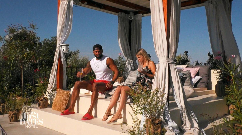 Öczan und Jacqueline sitzen auf einer Liege am Pool des Fist Dates Hotel