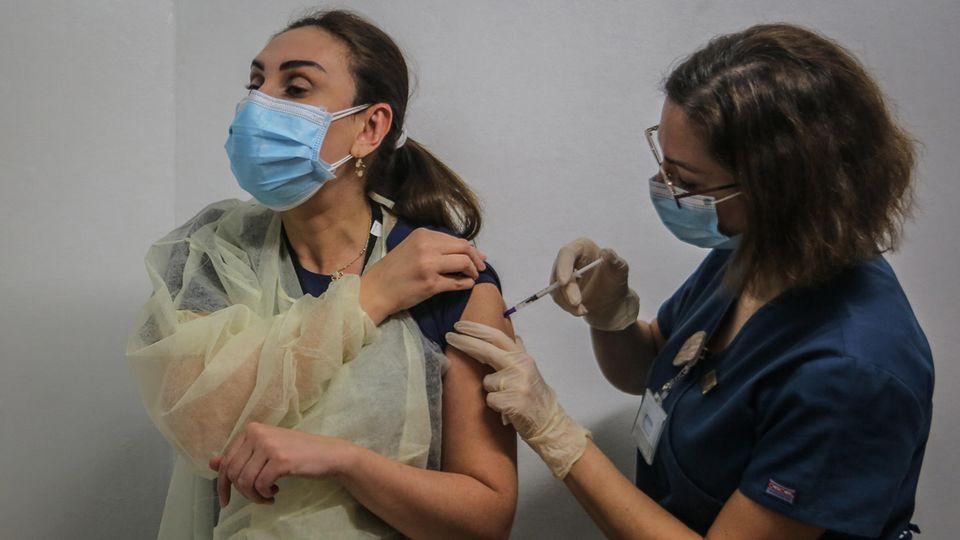 Impfung gegen das Coronavirus: Eine Frau bekommt den Impfstoff verabreicht