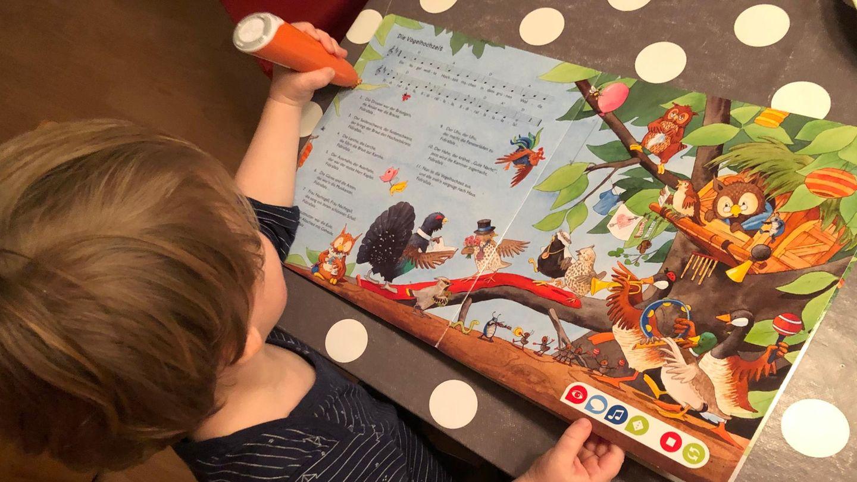 Tiptoi Starterset: Kleinkind sitzt am Tisch und spielt mit einem Tiptoi Buch