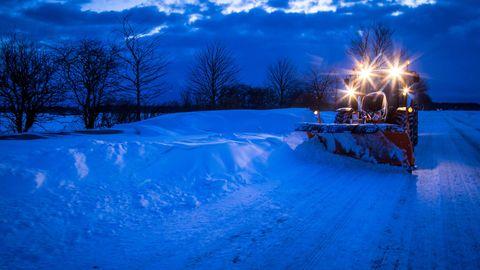 Ein Traktor mit Schneepflug räumt eine Straße frei