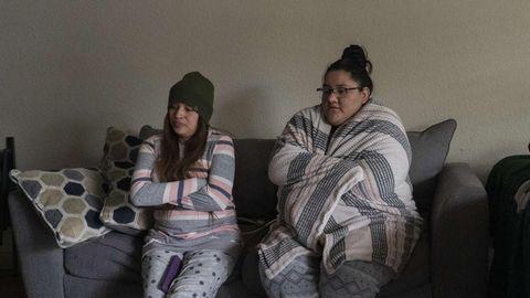 Zwei Frauen sitzen in bequemer Kleidung und in Decken gehüllt auf einem Sofa in Texas