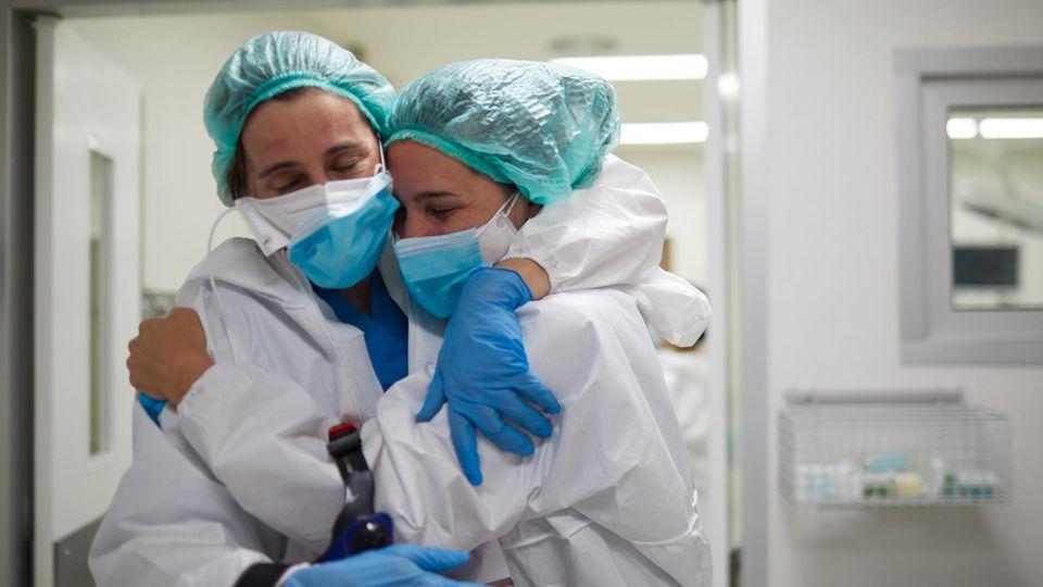 Zwei Pflegekräfte in Schutzmontur umarmen sich innig.