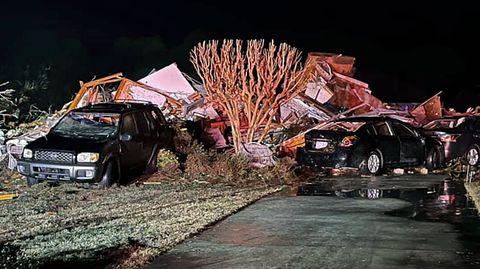 Zwei schwarze Pkw stehen demoliert neben den Trümmern eines Hauses