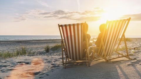 Urlauber sitzen in Liegestühlen an einem Strand