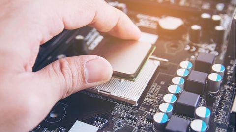 Intel vs. AMD: Eine CPU wird in den Sockel gelegt.