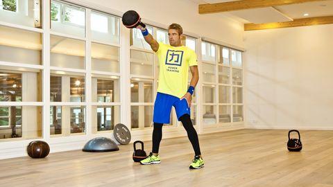 Kettlebell Workout: Ex-Triathlon-Profi Max Longrée trainiert mit Kettlebell in einem Fitnessraum