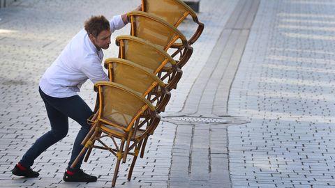 Ein Mitarbeiter eines Straßencafes trägt gegen 15 Uhr aufeinander gestapelte Stühle in sein Lokal