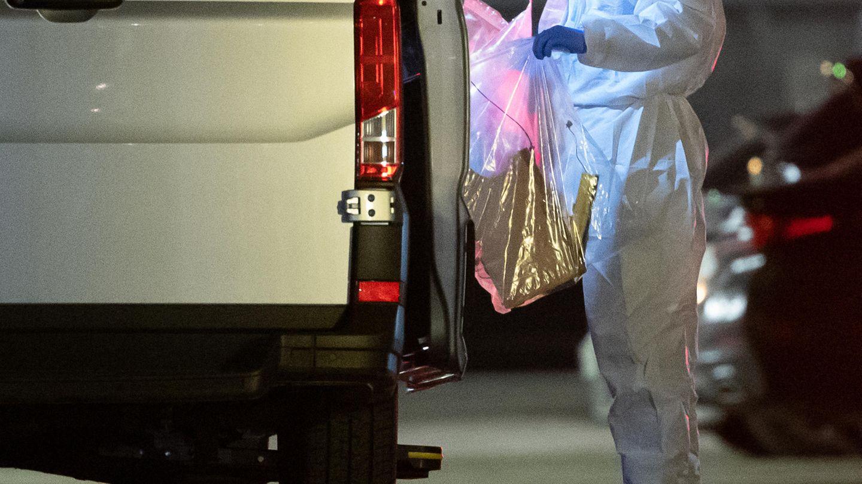 Ein Kriminaltechniker bringt einen Plastikbeutel zum Wagen
