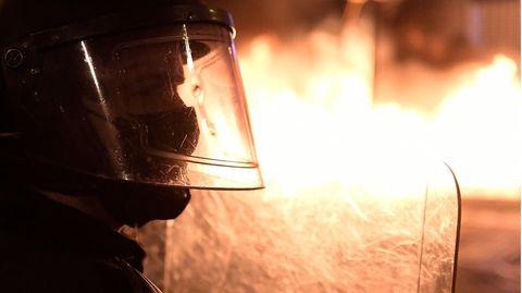 Ein Polizist mit Schutzhelm und Schild ist im Profil zu sehen. Er zeichnet sich dunkel gegen den Feuerschein hinter ihm ab