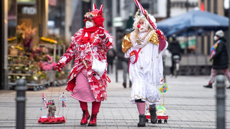 Zwei Frauen mit Mundschutz beim Kölner Karneval.