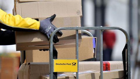 Postgesetz - Ein Paketbote lädt Pakete von einem Wagen