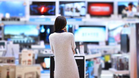 Eine Frau überlegt, welche Angebote sich im Media Markt Prospekt lohnen.