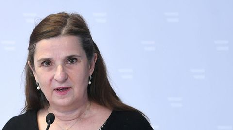Eine weiße Frau mit langen braunen Haaren und in schwarzem Pullover mit V-Ausschnitt spricht in ein Mikrofon