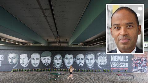 Eine Frau geht vor Porträts von Opfern des Anschlags von Hanau entlang