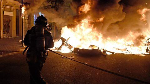 Ein Feuerwehrmann mit Atemluft-Tank auf dem Rücken nähert sich mit Schlauch in den Händen einem brennenden Auto