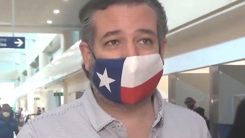 Ein Mann mit Mund-Nasen-Schutz im Look der Flagge von Texas geht durch ein Flughafen-Terminal