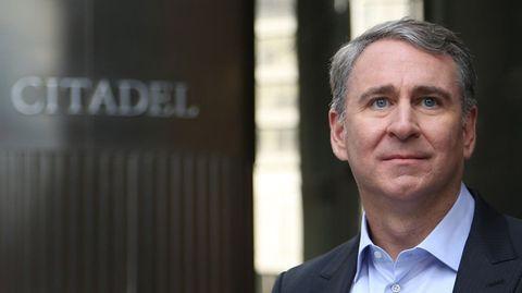 """Ein weißer Mann mit grauem Seitenscheitel steht im schwarzen Anzug neben einem silbernen """"Citadel""""-Schriftzug mit Logo"""