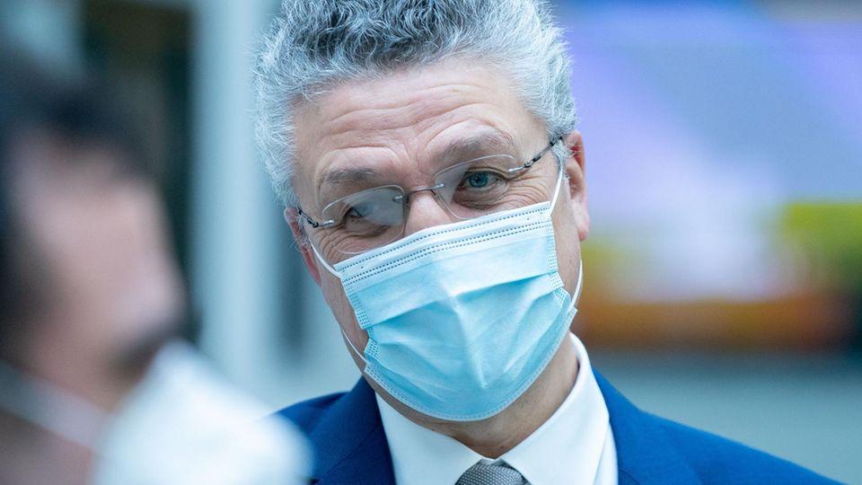 Ein Mann mit grauen Locken, randloser Brille und blauem Anzug trägt eine OP-Maske und legt den Kopf leicht schräg