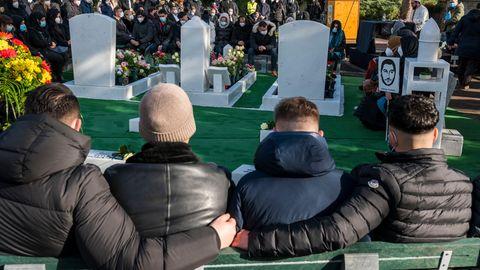 Von hinten sind vier junge Männer auf Stühlen zu sehen. Sie sitzen mit Blick auf vier Grabsteine und umarmen einander