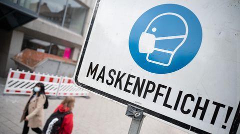 """Zwei Passantinnen gehen in einer Fußgängerzone hinter einem Schild vorbei, auf dem """"Maskenpflicht"""" steht"""